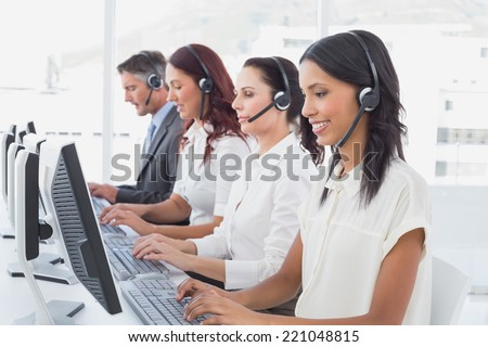 Employee's typing on their computers using headsets - stock photo