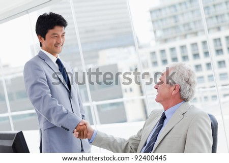 Employee shaking the hand of his manager in an office