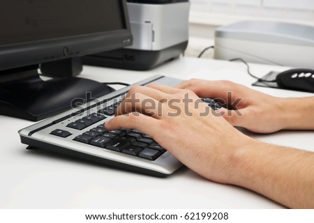 Employee typing on keyboard in office - stock photo
