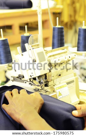 Employee working on an industrial sewing machine - stock photo