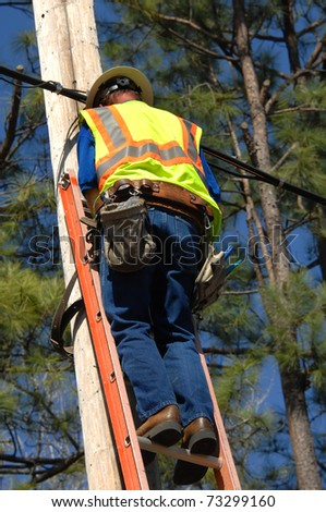 Employee works on power line on a sunny day with blue skies.  He is wearing safety equipment including belt and neon vest. - stock photo