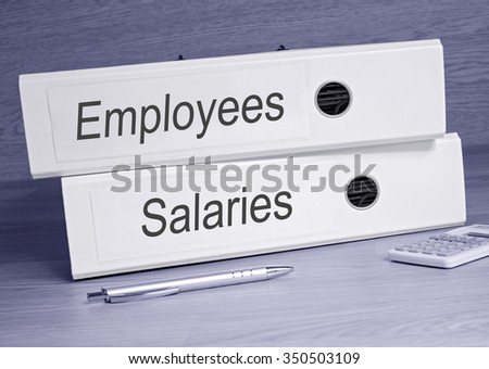 Employees and Salaries - two white binders on desk in the office