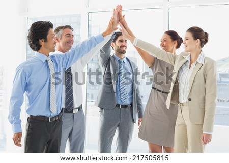 Employees celebrating a good job with a high five - stock photo