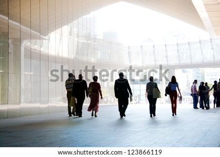 Employees going against the office. Panorama. Silhouettes. - stock photo