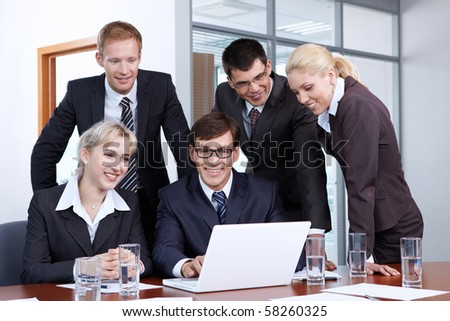 Employees of the office looking at laptop monitor - stock photo
