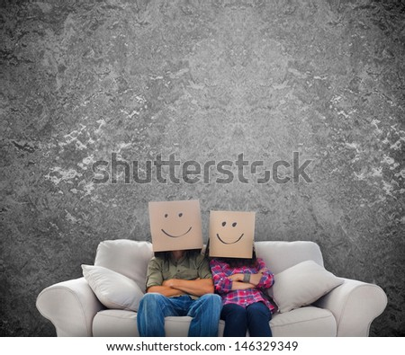 Employees sat on a couch wearing boxes on their heads with an old wall on the background - stock photo