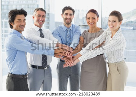 Employees smiling and having fun while stacking hands together - stock photo