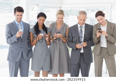 Employees using their mobile phone in the office - stock photo