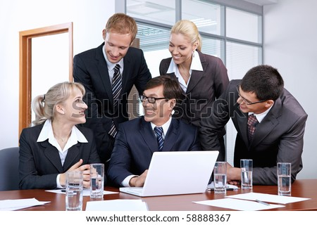 Employees with boss laughing at work - stock photo