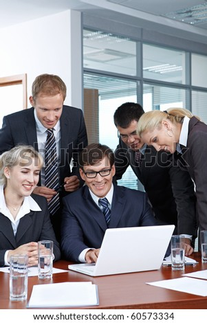 Employees with the boss looking at laptop monitor - stock photo