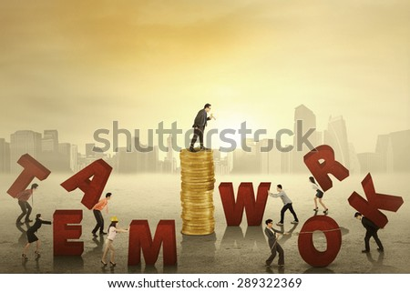 Employees working together to arrange a text of teamwork with their boss giving order from the stack of golden coins - stock photo
