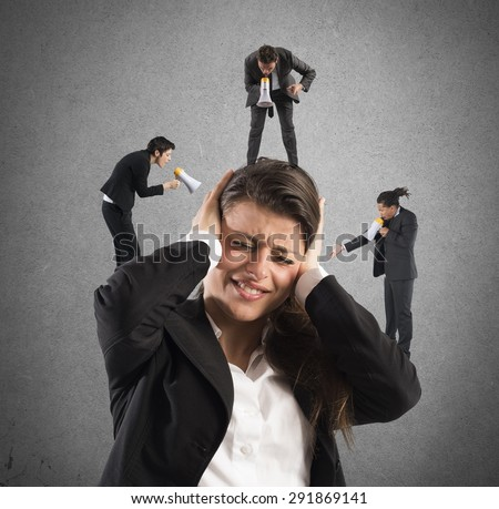 Employees yelling to a businesswoman with megaphone - stock photo