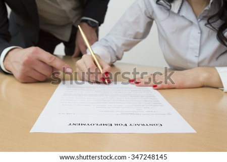Employer showing new employee where to sign employment contract - stock photo