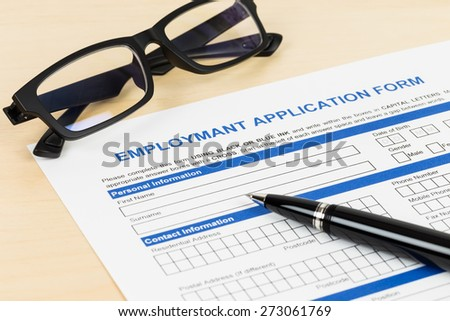 Employment application form with pen and glasses; form is mock-up