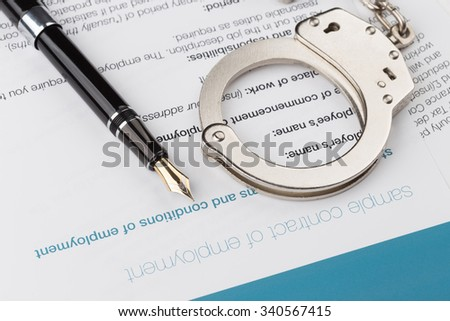 employment contract with fountain pen and handcuffs - stock photo