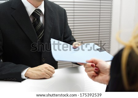Employment interview with female applicant handing over a file containing her curriculum vitae to the businessman - stock photo