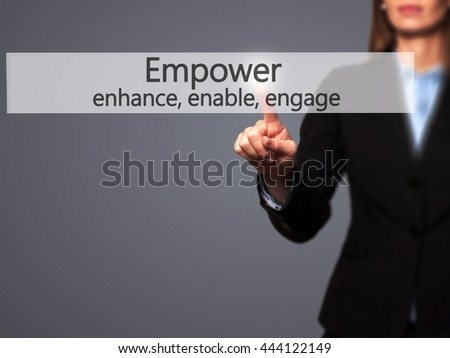 Empower enhance, enable, engage - Businesswoman hand pressing button on touch screen interface. Business, technology, internet concept. Stock Photo