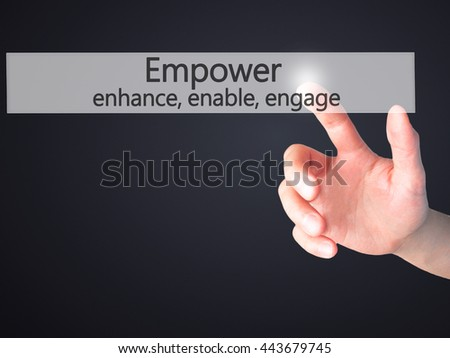 Empower enhance, enable, engage - Hand pressing a button on blurred background concept . Business, technology, internet concept. Stock Photo