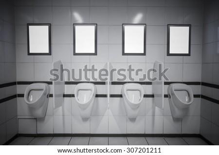 Empty advertisement frames in public toilet - stock photo