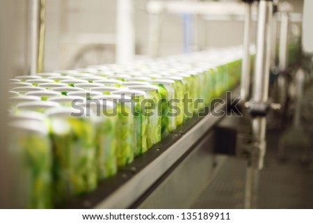 Empty aluminum cans for drinks move on conveyor at large factory. Shallow depth of field. - stock photo