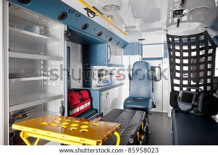 Empty ambulance interior with equipment on bench - stock photo