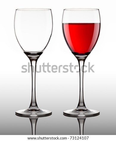 empty and full glass goblet with red wine on gray background - stock photo