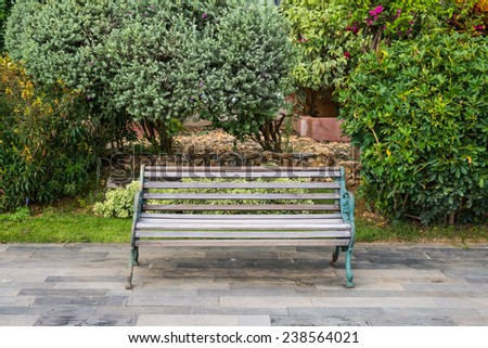 Empty and lonely wooden bench in the city park - stock photo