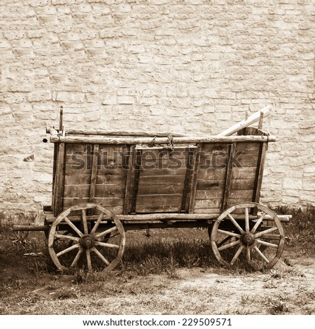 Empty and old wooden cart on background of brick wall - stock photo