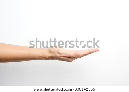 Empty Asian female hand on white wall - stock photo