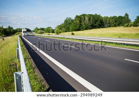 Empty asphalt expressway with white truck arriving from afar in the countryside. Sunny day. - stock photo