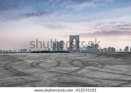 empty asphalt floor with city skyline