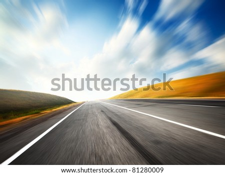 Empty asphalt road and blue sky with blurred clouds - stock photo