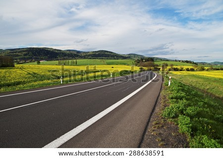Empty asphalt road between yellow flowering rapeseed field in rural landscape. Wooded mountains in the background. - stock photo