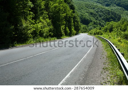 Empty asphalt road highway in the forested mountains