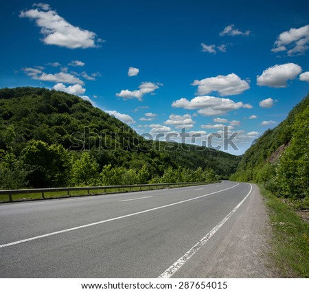 Empty asphalt road highway in the forested mountains, on the background a cloudy sky - stock photo