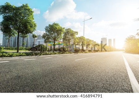 empty asphalt road in modern city at sunrise - stock photo