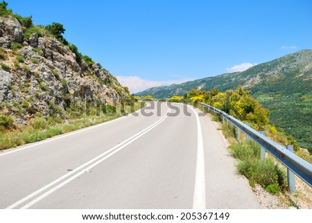 Empty asphalt road in the green hills with blue sky - stock photo