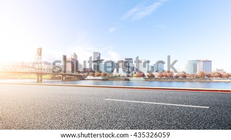 empty asphalt road near water with cityscape and skyline of portland at sunrise - stock photo