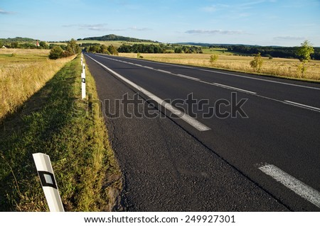 Empty asphalt road through the fields towards the horizon in a rural landscape, wooded mountain on the horizon - stock photo