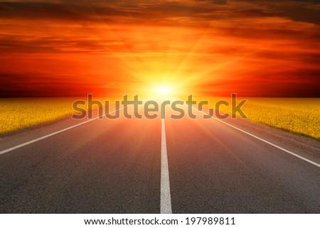 Empty asphalt road to sunset - stock photo