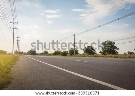 Empty asphalt road under cloudy sky - stock photo