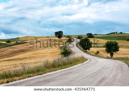 Empty asphalt road winding into the distance through hills through agricultural farmland on a cloudy day - stock photo
