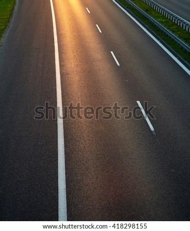 Empty asphalt road with sun reflection - stock photo