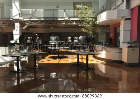 Empty Atrium with chairs on the tables, lit by giant skylights reflecting off the stained concrete floor - stock photo