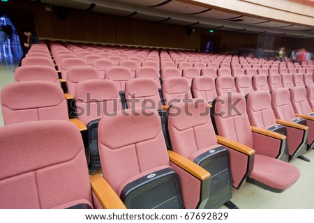 empty auditorium with red chairs, theatre or conference hall - stock photo