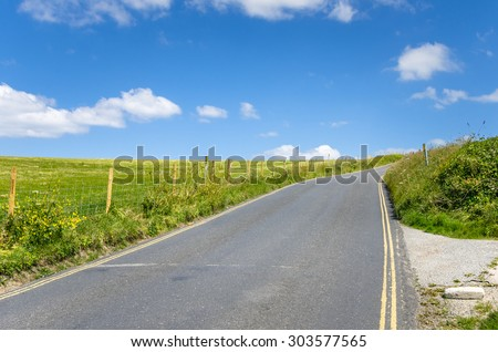 Empty Back Road in Cornwall and Blue Sky - stock photo