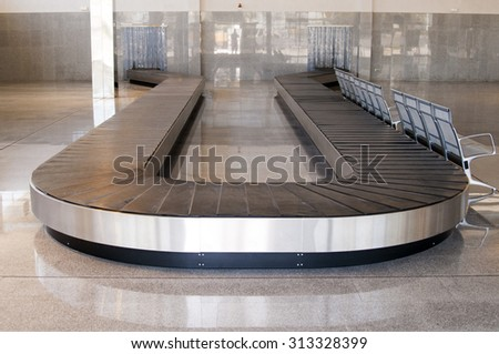 empty baggage carousel in airport hall with granite floor-Baggage claim area, transporter belt - stock photo