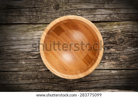 Empty bamboo bowl on wooden background - stock photo