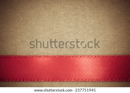 Empty banner on vintage background. Red ribbon on brown fabric cloth texture with copy space. - stock photo