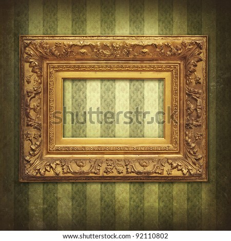 Empty baroque golden frame on Victorian floral green-gold stripe - stock photo